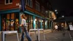 A woman packs up an outdoor bar area in Manchester