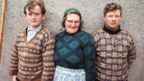 A woman and two men pose wearing Fair Isle jumpers in front of the wall of a cottage on one of the Shetland Islands in 1970.