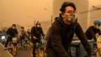 People wear protective masks as they cycle during a sandstorm on 15 March 2021 in Beijing