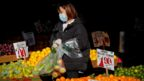A woman wears a mask and gloves as he shops at a fruit stand
