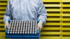 A person in a clean suit holding a tray of batteries (Credit: Alamy)