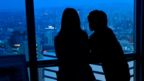 Silhouette of man and woman looking out window at view of Japan