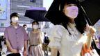 Pedestrians wearing face masks walk across the Shinjyuku shopping street in Tokyo on 28 July 2021