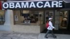 A pedestrian walks past the Leading Insurance Agency, which offers plans under the Affordable Care Act, in Miami