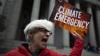 A protester shouts slogans and holds a climate emergency placard protesting against Exxon Mobil before the start of a trial the company faced in 2019.
