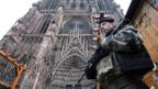 An armed soldier stands outside a cathedral in Strasbourg
