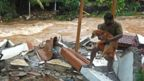 A resident carries a dog amid debris of his damaged house after flash floods caused by heavy rains at Thodupuzha in India's Kerala state, 16 October 2021