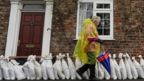A woman walks past sand bag flood defences in the village of Naburn near York as water levels rise on the River Ouse.