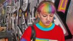 A young woman with dyed hair looks at her mobile phone