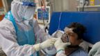 A doctor and a nurse wearing Personal Protective Equipment (PPE) suits look after a COVID-19 coronavirus patient at the Intensive Care Unit of the Sharda Hospital, in Greater Noida. -