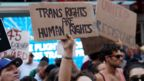 People protest President Trump's announcement he plans to reinstate a ban on transgender individuals from serving