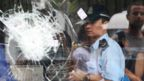 Hong Kong police officer seen through shattered glass