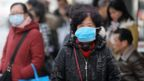 Chinese residents wear masks while waiting at a bus station near the closed Huanan Seafood Wholesale Market in Wuhan