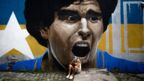 A woman cries in front of a mural of Diego Maradona, in Buenos Aires