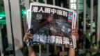An employee holds up the latest copies of the Apple Daily newspaper