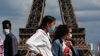 People wearing protective face masks walk at the Trocadero square near the Eiffel Tower in Paris