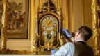 Horological conservator Fjodor van den Broek adjusts a clock