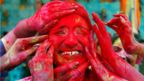 A woman reacts as devotees apply coloured powder on her face during celebrations for Holi outside a temple on the outskirts of Kolkata, India, 21 March 2019.
