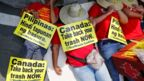 Demonstrators hold placards while lying down during a protest at the Canadian Embassy in the Philippines