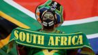 A woman wears South African football colours and the national flag.