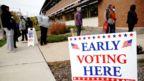 People queue to enter a polling site at the Milwaukee Public Library's Washington Park location in Milwaukee, on the first day of early voting in Wisconsin, October 20, 2020.
