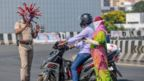 Police inspector Rajesh Babu (left) wearing a coronavirus-themed helmet speaks to motorists during a government-imposed nationwide lockdown as a preventive measure against the COVID-19 coronavirus in Chennai on 28 March 2020
