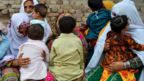 Parents nervously watch over their children as they jostle in line to be tested for HIV in a village near Pakistans Larkana amid a sudden outbreak among its young