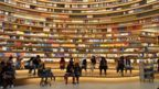 Students sitting and reading against background of towering shelves stacked with books