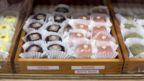 Rows of assorted mochi in various wooden crates
