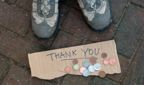 Pair of shoes and a piece of cardboard with Thank You written on it and some coins scattered underneath