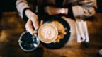 Image shot above of hand holding coffee mug with latte art of fern