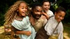 Man carrying children who are laughing and smiling in still from film Come Away