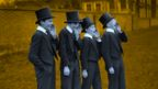 Black and white image of Eton pupils in top hats