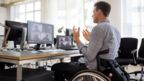 Man in wheelchair gesticulating as he speaks to people on teleconference screen