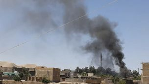 Smoke rises from houses during fighting in Qala-e- Naw, the capital of Badghis province, on July 7, 2021