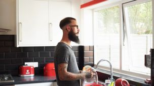Bearded man in spectacles looks outside kitchen window while drying cutlery